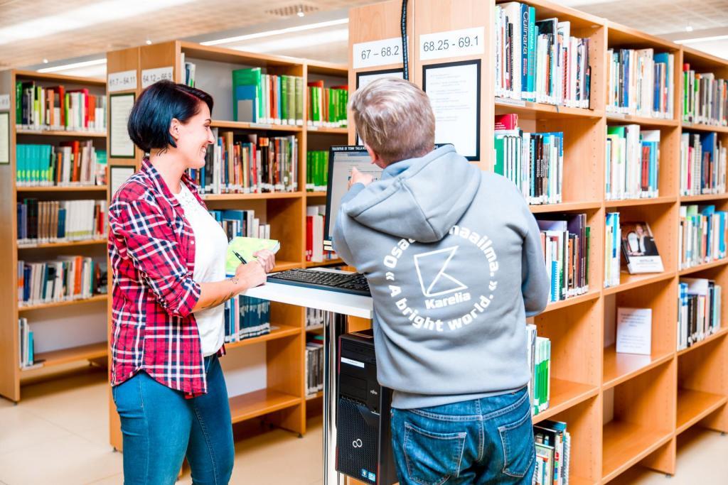 kirjastohenkilökunta opastaa asiakasta